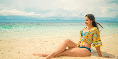 Woman sitting on the beach in the Philippines traveling for under $1000 a month