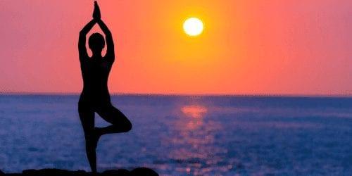 Girl doing yoga at sunset
