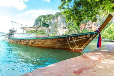 Longtail boat in Railay Beach Thailand with Limestone cliffs in the background on Chase Your Adventure Tours