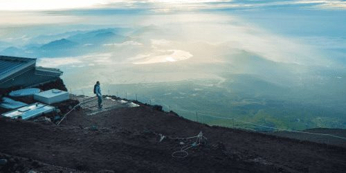Man Climbing Mt Fuji with the View from the summit