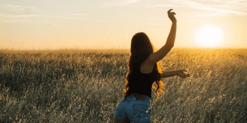 Girl in a field of wheat at sunset