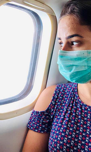 A girl with a mask looking out the window of an airplane during the COVID-19 Pandemic